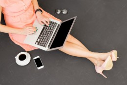 Modern female having coffee and using computer
