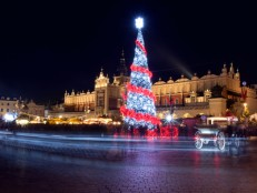 Krakow, Poland, Main Market square and Cloth Hall in winter, during Christmas fairs decorated with Christmas tree.